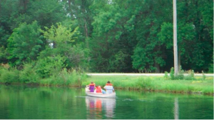 Camp Catch Up guests canoe on the camp's pond